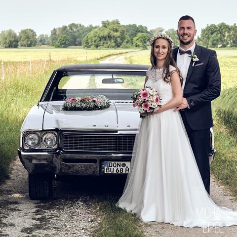Brautpaar vor Hochzeitsauto – Hochzeitsfotografie